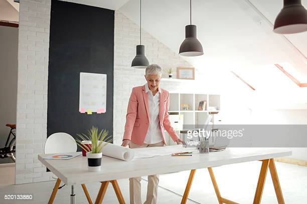 Mature Architect working in her office.