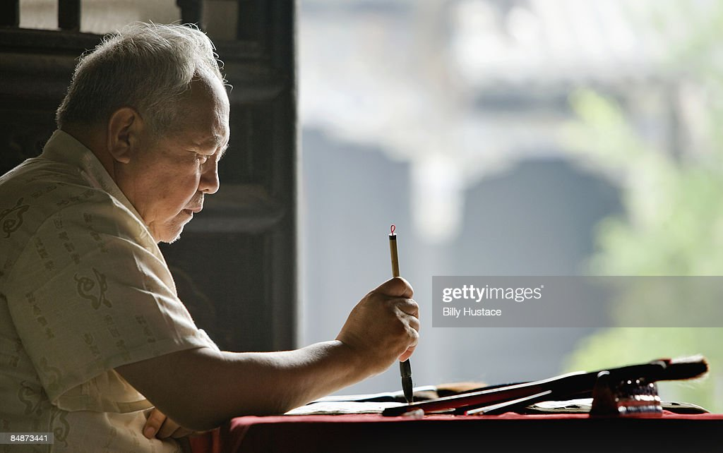 Mature artist painting Chinese calligraphy.