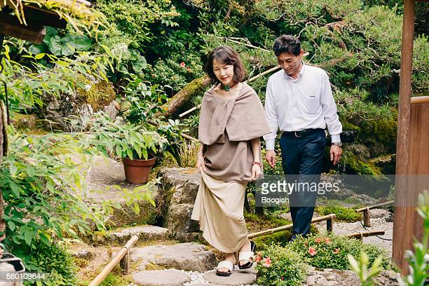 Mature Asian Couple Walking Together in Japanese Garden Kyoto Japan