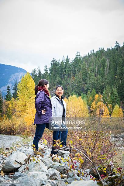 Mature Asian Mother and Teenage Daughter Hiking in the Wilderness