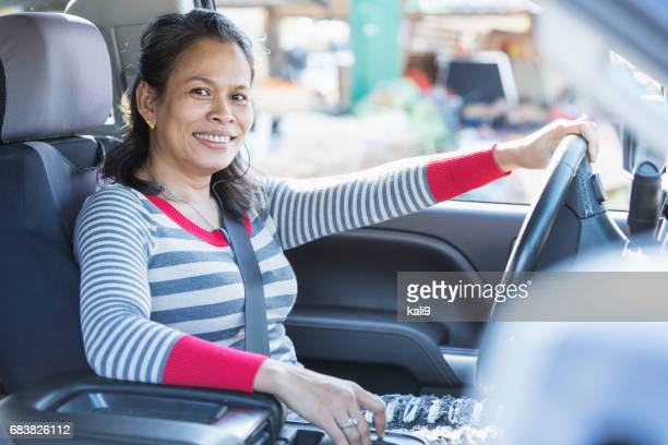 Mature Asian woman driving a pick-up truck
