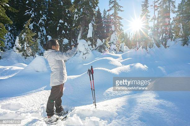 Mature Asian Woman Taking Cellphone Photo While Hiking with Snowshoes