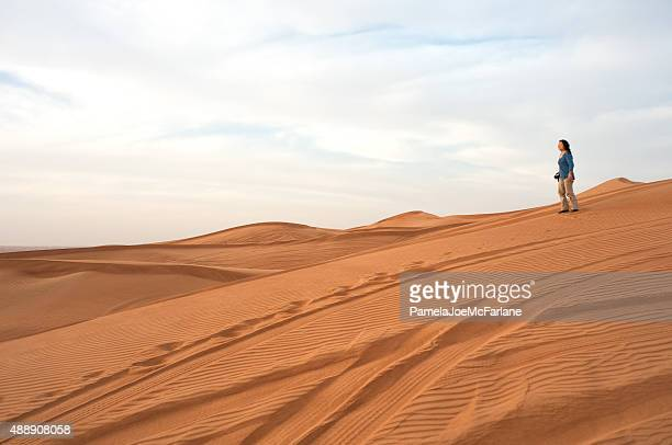 Mature Asian Woman Tourist with Camera on Sand Dune, Dubai