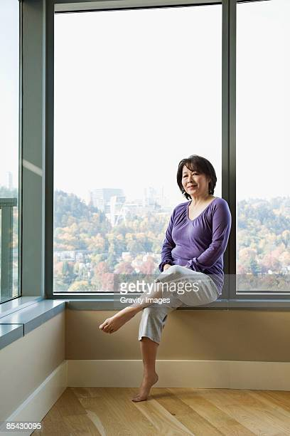 Mature asian women sitting on window sill