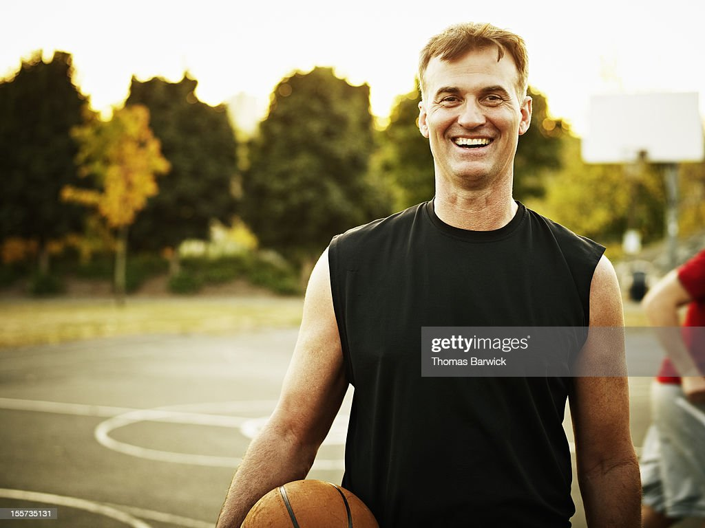 Mature basketball player standing on outdoor court : Stock Photo