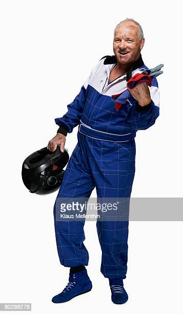 Mature biker holding helmet clenching fist, portrait
