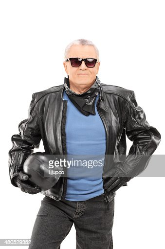 Mature biker in a leather jacket holding a helmet : Stock Photo
