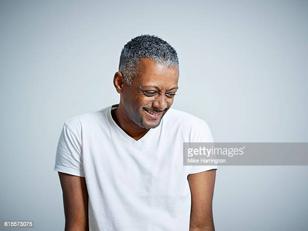 Mature black male looking down and smiling
