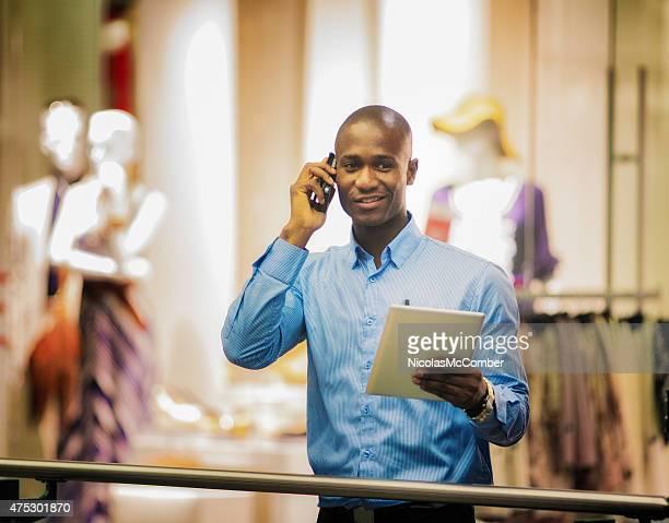 Maduro homem sorridente preto enquanto no telefone em mall