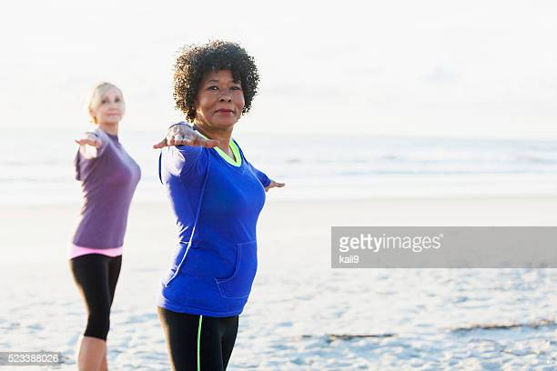 Mature black woman exercising on beach with friend