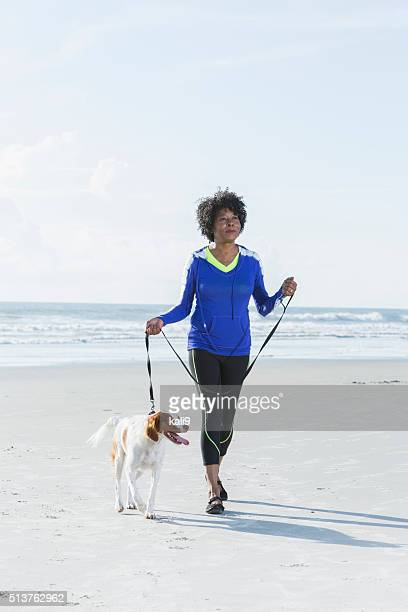 Mature black woman walking dog on beach