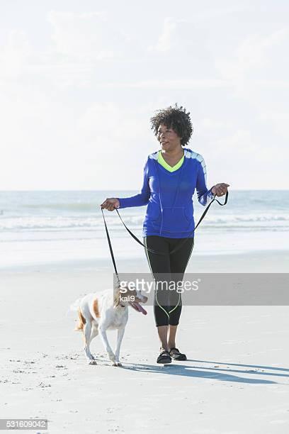 Mature black woman walking dog on beach