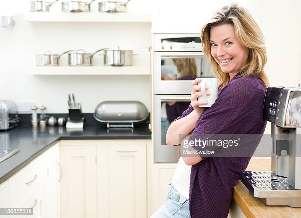 Mature blonde woman enjoying a cup of coffee at her home