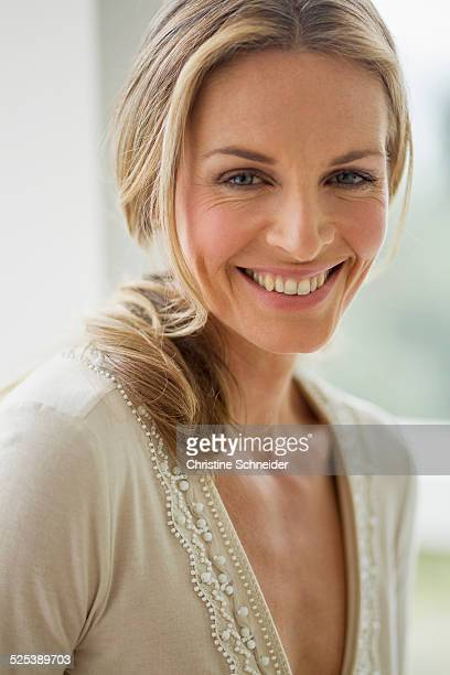 Mature blonde woman looking at camera smiling, portrait