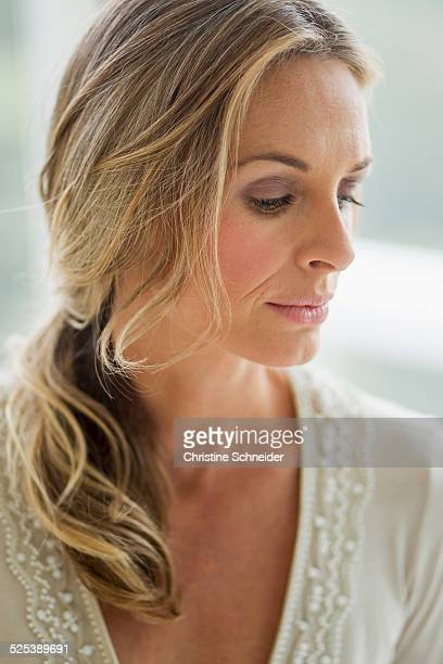 Mature blonde woman looking down, portrait