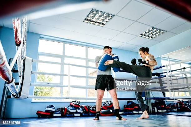 Mature boxer practicing with his coach at gym