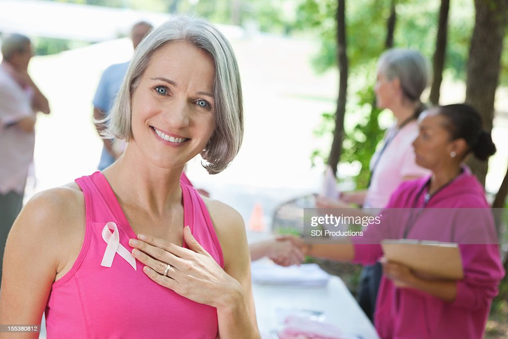 Mature breast cancer survivor signing up for outdoor charity race
