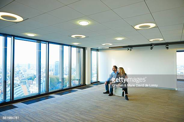 Mature business couple looking from empty office window at Brussels cityscape, Belgium