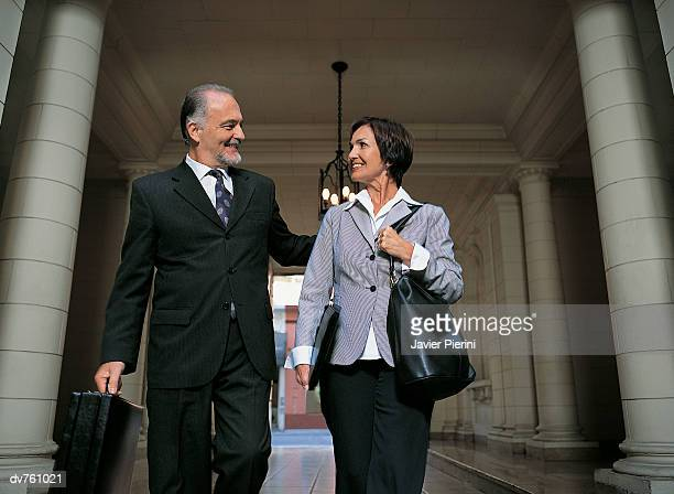 Mature Business Couple Walking in a Covered Walkway