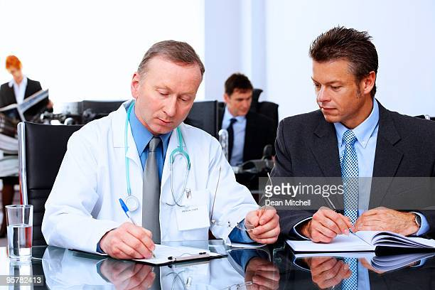 Mature Business group in modern office talking with a doctor