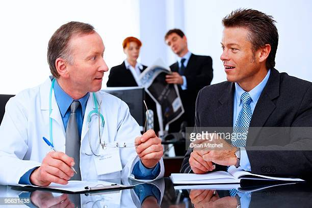 Mature Business group talking to a doctor in modern office