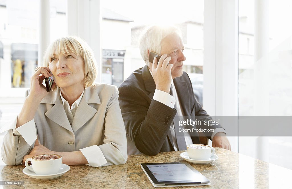 Mature business man and lady using smart phones : Stock Photo