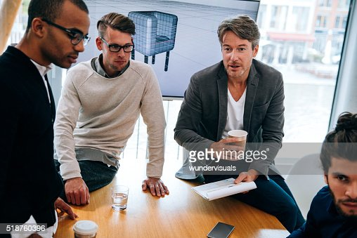 Mature business man giving notes to team from clipboard