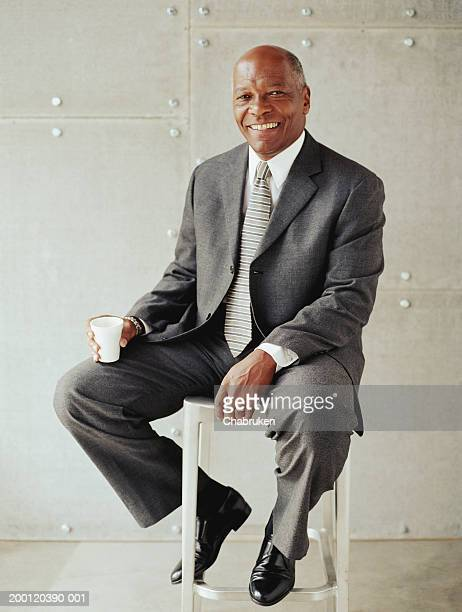 Mature business man sitting on stool holding cup of coffee, portrait