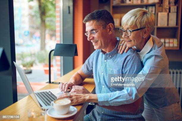 Mature business people working on laptop in a cafe