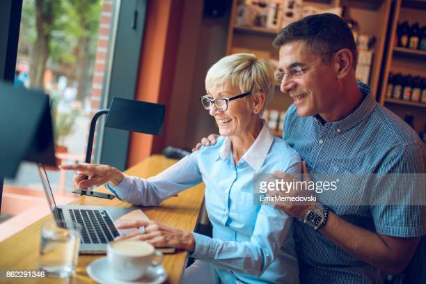 Mature business people working on laptop in cafe