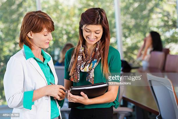 Femme d'affaires Mature parler aux stagiaires au bureau moderne