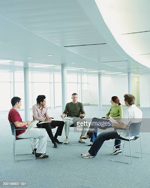Mature businessman addressing colleagues in empty office