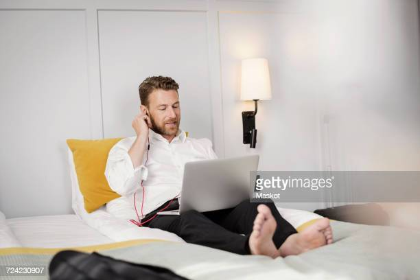 Mature businessman adjusting headphones while sitting on bed using laptop in hotel room