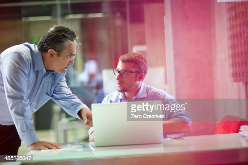 Mature businessman advising male office worker
