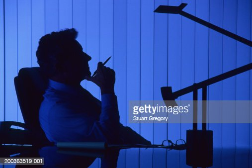 Mature businessman at desk, side view, silhouette : Stock Photo