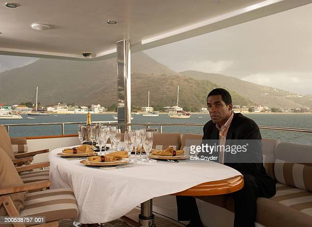 Mature businessman at dining table on yacht