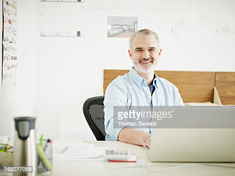 Mature businessman at laptop in startup office : Stock Photo