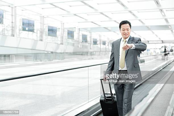 Mature businessman checking the time on airport escalator
