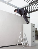 Mature businessman climbing on wall through filing cabinet in office