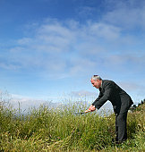 Mature businessman clipping grasses with shears, side view