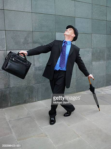 Mature businessman dancing along street with briefcase and umbrella