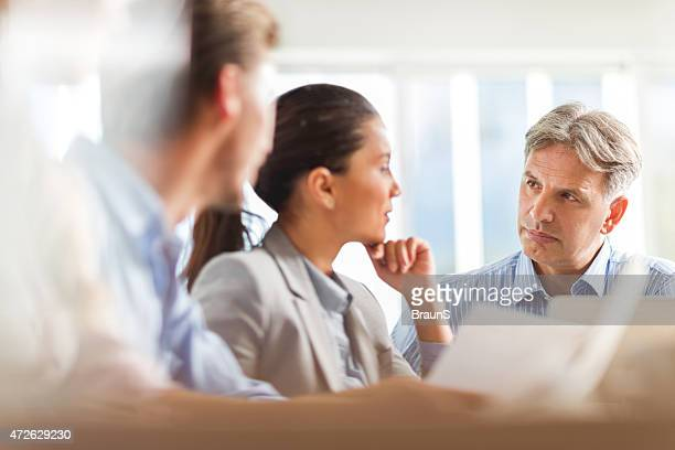 Mature businessman discussing with his female colleague during a meeting.