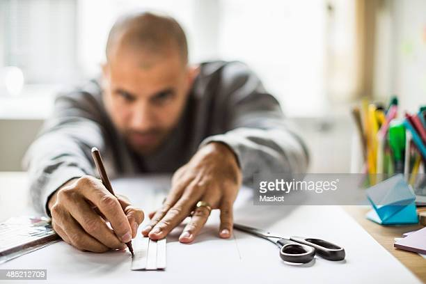 Mature businessman drawing line on paper at desk in creative office