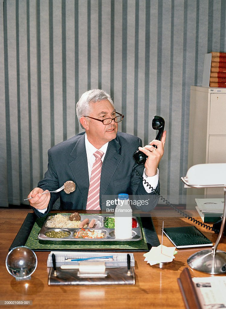 Mature businessman eating at desk, holding telephone receiver : Stock Photo