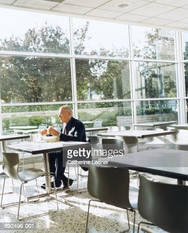 Mature businessman eating lunch in cafeteria : Stock Photo