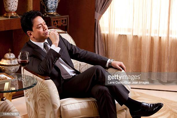 Mature businessman enjoying cigar and wine in a luxurious room