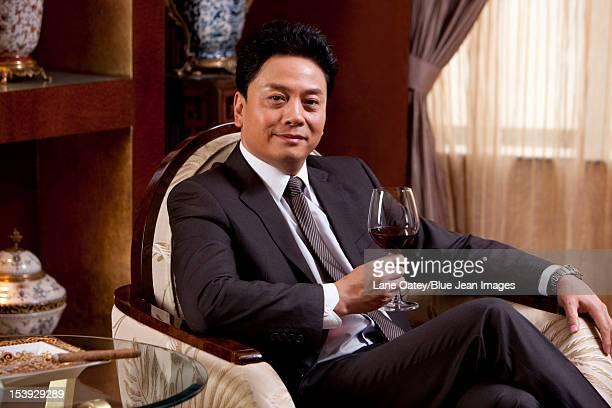 Mature businessman enjoying wine in a luxurious room