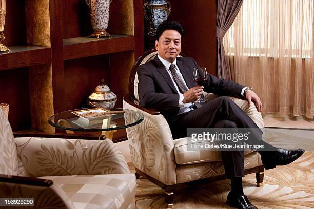 Mature businessman enjoying wine in a luxurious room