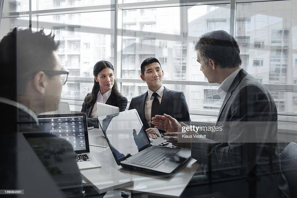 Mature businessman explaining to younger people : Stock Photo