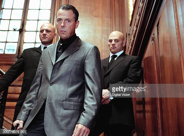 Mature businessman flanked by two security guards in panelled room, portrait